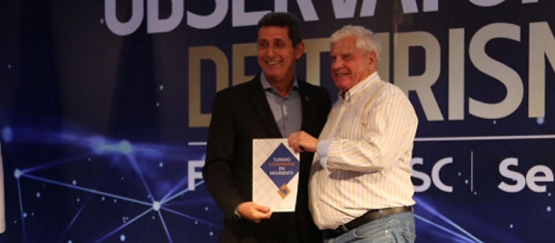 João Eduardo Amaral Moritz entrega a Ricardo Siqueira um exemplar do relatório do Turismo Catarinense