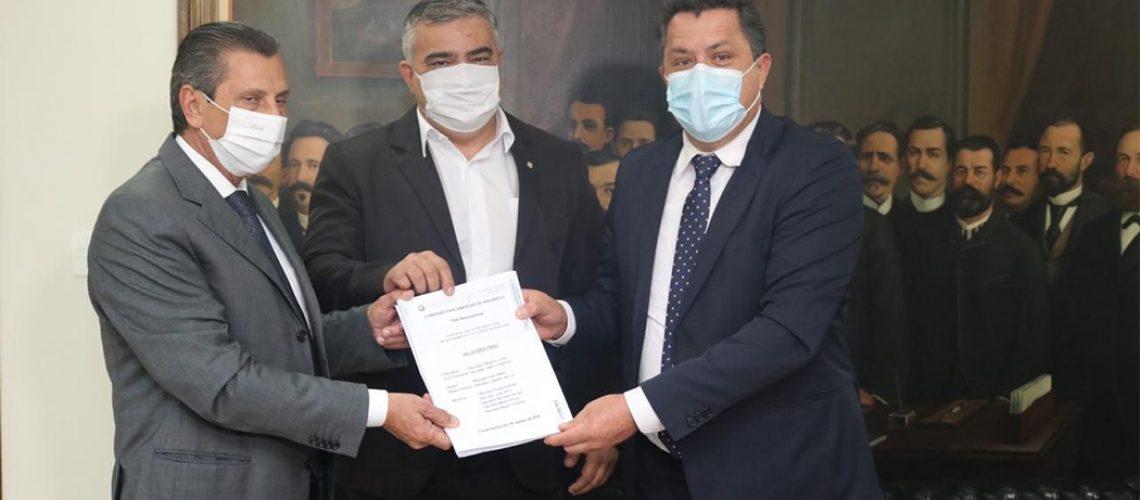 Os deputados Sargento Lima (PSL) e Ivan Naatz (PL), respectivamente presidente e relator da CPI dos Respiradores, entregam o documento ao presidente da ALESC deputado Julio Garcia o Foto: Raffael do Prado